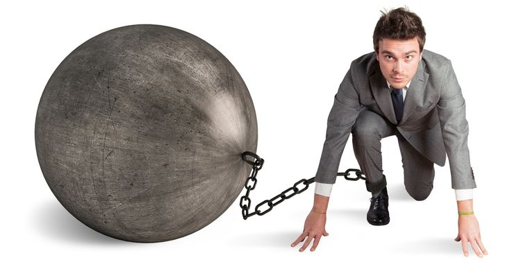 Photo of a businessman in low runner start with large prison ball and chain attached to his ankle