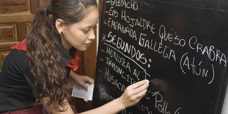 Photo of a girl writing a menu board at the restaurant