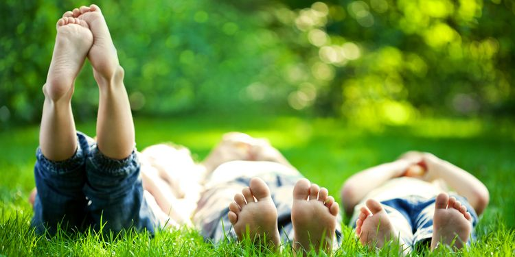 Photo of children lying in grass outdoors