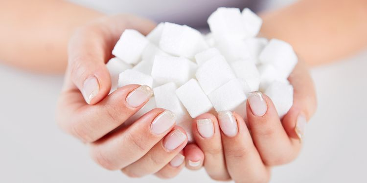 Photo of sugar cubes in hands