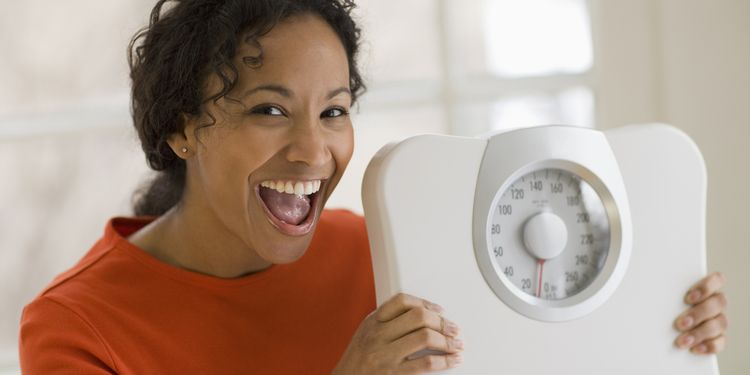 Photo of happy woman with weight scale