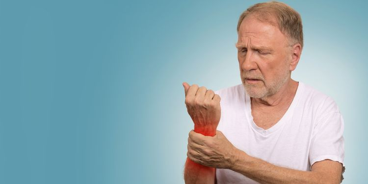 Photo of a man holding his inflamed wrist joint