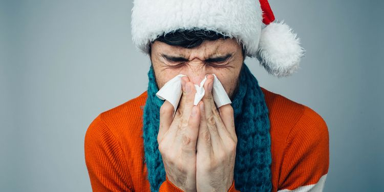 Photo of a sneezing man in a Santa Claus Suit