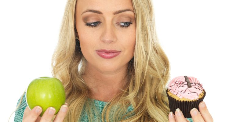 Photo of a woman undecided what to eat - apple or a cake