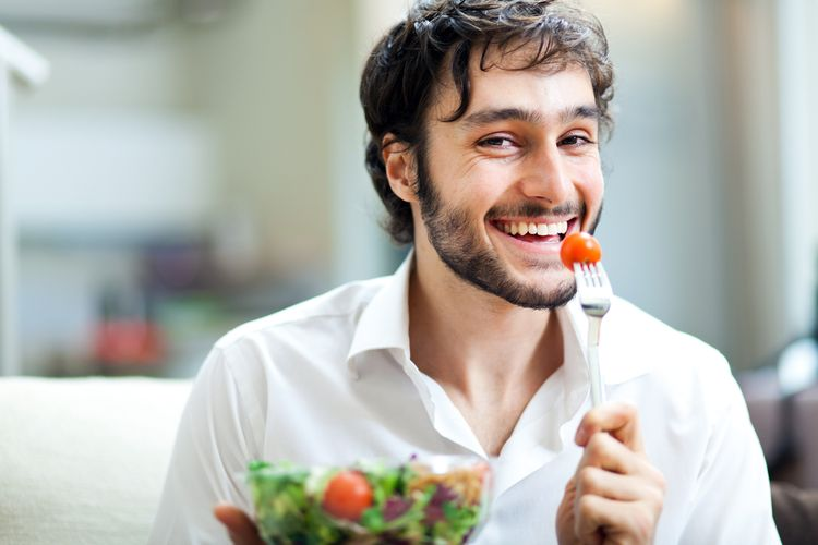 Photo of a smiling young man eating cherry tomato