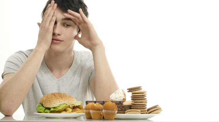 Photo of a man looking at the fast food rich in gluten that causes addiction