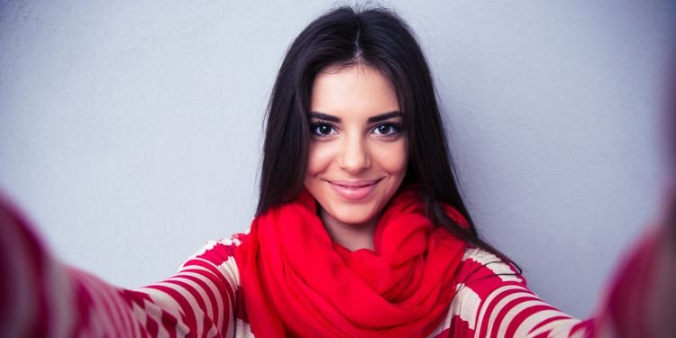 Photo of a young woman staring at the camera smiling