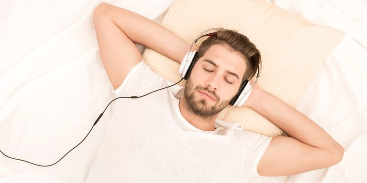 Photo of a man listening binaural beats in bed through head set