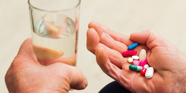 Photo of an old persons hand holding glass of water and pills