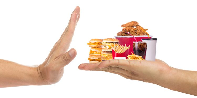 Photo of a hand holding on palm various junk foods and other hand refusing