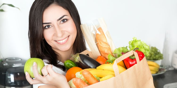 Photo of a young woman smiling and holding bag of vegetables