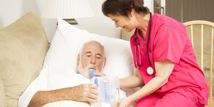 Photo of an ill old person lying in bed with nurse doing breathing test