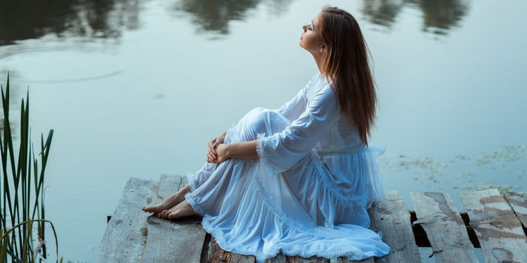 Photo of a woman sitting near river and chanting mantra