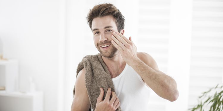 Photo of a man applying natural body wash on his face