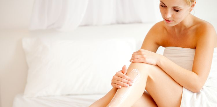 Photo of a woman applying moisturizer on her legs