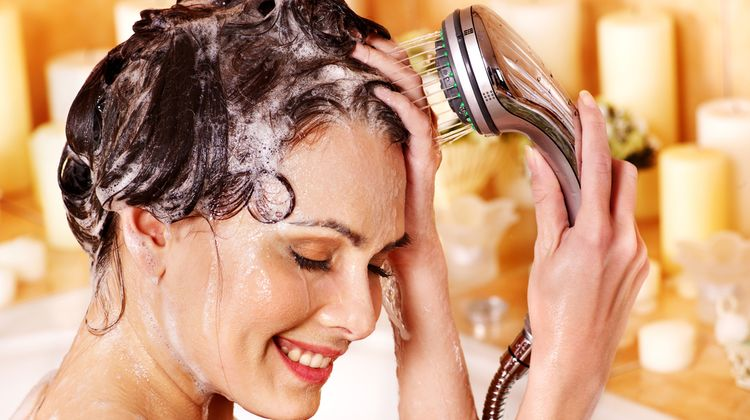 Photo of a woman washing her hair in shower