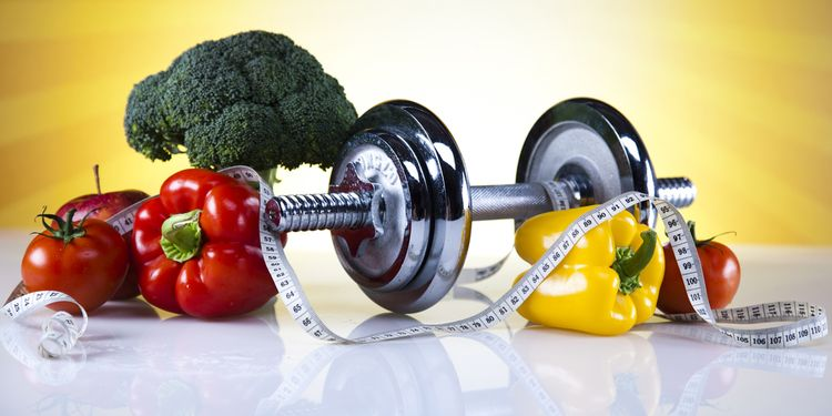 Photo of a weight set surrounded by raw vegetables