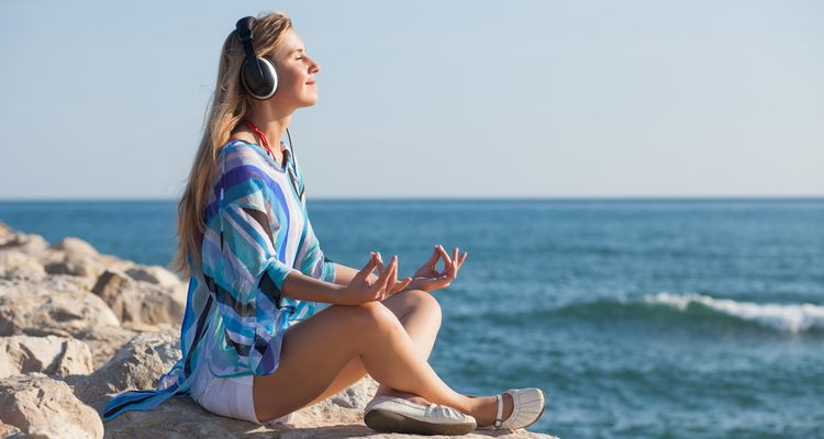 Photo of a woman meditating on a sea coast and listening music through headset